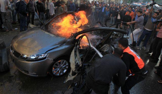 I palestinesi spengono l'incendio della macchina di Ahmed Jabari, capo dell'ala militare del movimento Hamas dopo che è stato colpito da un attacco aereo israeliano a Gaza il 14 novembre 2012.