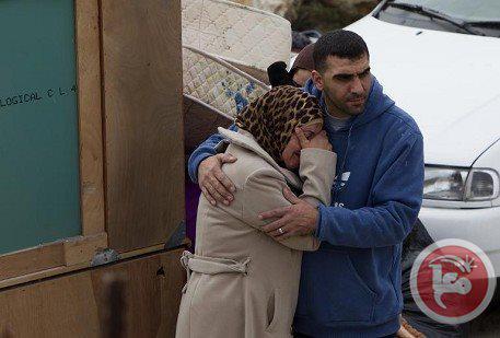 Una donna è confortata da un parente mentre guardano le scavatrici israeliane demolire la loro [casa],nel sobborgo di Beit Hanina a Gerusalemme est, 27 genn. 2014. (AFP/Ahmad Gharabli)