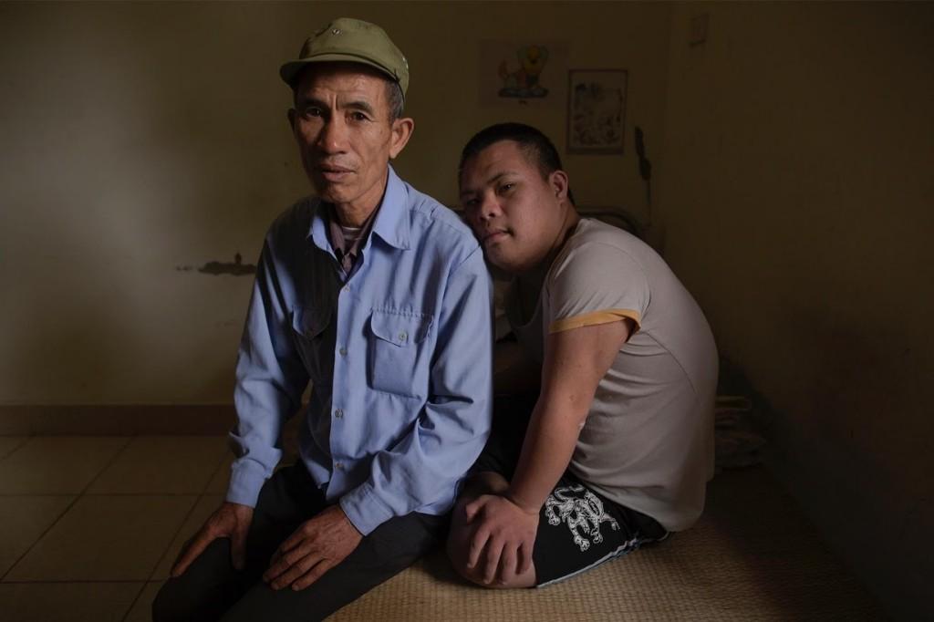 L'ex-soldato Nguyen Hong Phuc, 63enne, è seduto sul letto con suo figlio Nguyen Dinh Loc, 20enne.